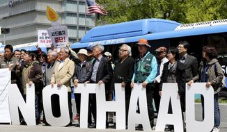 """Protesters hold letters reading """"NO THAAD"""" during a rally to oppose a plan to deploy an advanced U.S. missile defense system called Terminal High-Altitude Area Defense, or THAAD, near U.S. Embassy in Seoul, South Korea, Wednesday, April 26, 2017. In a defiant bit of timing, South Korea announced Wednesday that key parts of a contentious U.S. missile defense system had been installed a day after rival North Korea showed off its military power. (AP Photo/Lee Jin-man)"""
