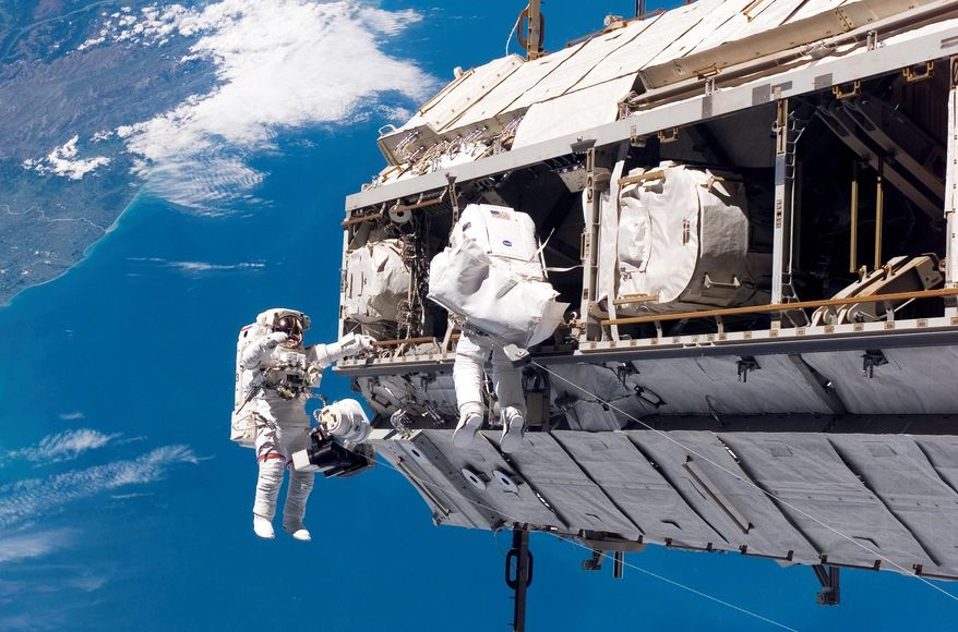 In this Dec. 12, 2006 photo made available by NASA, astronaut Robert L. Curbeam Jr., left, and European Space Agency astronaut Christer Fuglesang, participate in a spacewalk during construction of the International Space Station. In the background are New Zealand and the Pacific Ocean. According to a report released Wednesday, April 26, 2017, NASA is managing a variety of design and health risks associated with the spacewalking suits used by astronauts aboard the International Space Station. The suits were developed more than 40 years ago and intended for only 15 years' use. (NASA via AP)