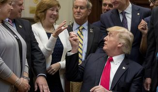 President Donald Trump gives his pen to a teacher from Virginia after signing the Education Federalism Executive Order during a federalism event in the Roosevelt Room of the White House in Washington, Wednesday, April 26, 2017. (AP Photo/Andrew Harnik)