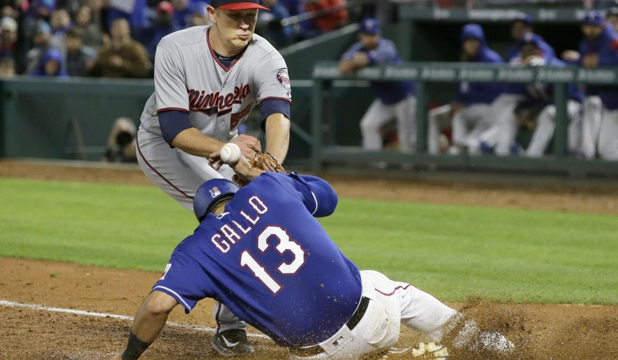 Minnesota Twins relief pitcher Tyler Duffey, can't handle the ball allowing Texas Rangers Joey Gallo (13) to score on a wild pitch during the sixth inning of a baseball game in Arlington, Texas, Wednesday, April 26, 2017. (AP Photo/LM Otero)