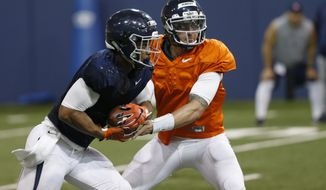 FILE - In this April 6, 2017, file photo, Virginia quarterback Kurt Benkert hands off to tailback Jordan Ellis during spring football practice in Charlottesville, Va. Benkert was hampered for much of last year after separating his left shoulder, and by a clunky brace protecting his surgically repaired right knee. (AP Photo/Steve Helber, File)