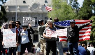 Demonstrators hold signs and flags Thursday, April 27, 2017, in Berkeley, Calif. Demonstrators gathered near the University of California, Berkeley campus amid a strong police presence and rallied to show support for free speech and condemn the views of Ann Coulter and her supporters. (AP Photo/Marcio Jose Sanchez)
