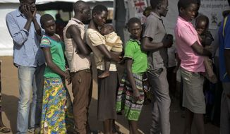 In this Thursday March 30, 2017 photo, South Sudanese refugee Mary Kide and her son, Desem, stand in line with others, including Samson Tabani, left, to get a medical check up at the Kuluba transit camp. The civil war in South Sudan has killed tens of thousands and driven out more than 1.5 million people in the past three years, creating the worlds largest refugee crisis. (AP Photo/Jerome Delay)