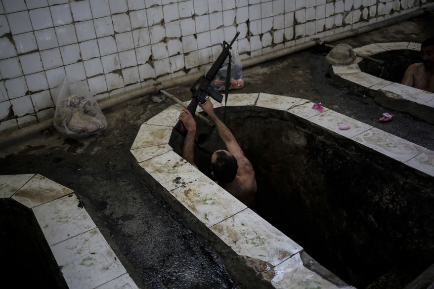 A federal police officer puts his machine gun on the edge of the bath in the Hamam Alil spa, south of Mosul, Iraq, Thursday April, 27, 2017. The spa reopened several months ago after the town was liberate from the Islamic State group. Many Iraqi soldiers visit the spa, located half an hour south of Mosul, in between fighting against the Islamic State group for relaxation. (AP Photo/Bram Janssen)