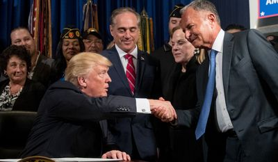 "President Donald Trump, left, accompanied by Veterans Affairs Secretary David Shulkin, center, shakes hands with Isaac ""Ike"" Perlmutter, an Israeli-American billionaire, and the CEO of Marvel, right, before signing an Executive Order on ""Improving Accountability and Whistleblower Protection"" at the Department of Veterans Affairs, Thursday, April 27, 2017, in Washington. Also pictured is Laura Perlmutter, second from right. (AP Photo/Andrew Harnik)"