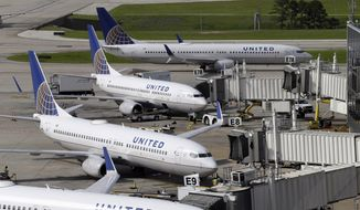 In this July 8, 2015, file photo, United Airlines planes are parked at their gates as another plane, top, taxis past them at George Bush Intercontinental Airport in Houston. United Airlines says it will raise the limit to $10,000 on payments to customers who give up seats on oversold flights and will increase training for employees as it deals with fallout from the video of a passenger being violently dragged from his seat. (AP Photo/David J. Phillip, File)
