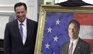 Former New Hampshire Gov. Craig Benson, left, poses with artist Richard Whitney during a ceremony where his official portrait was unveiled at the Statehouse in Concord, N.H., Thursday, April 27, 2017. Benson, a Republican, served one term as governor from 2003 to 2005. (AP Photo/Charles Krupa)
