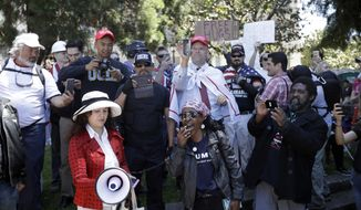 Demonstrators gather around a speaker Thursday, April 27, 2017, in Berkeley, Calif. Demonstrators gathered near the University of California, Berkeley campus amid a strong police presence and rallied to show support for free speech and condemn the views of Ann Coulter and her supporters. (AP Photo/Marcio Jose Sanchez)