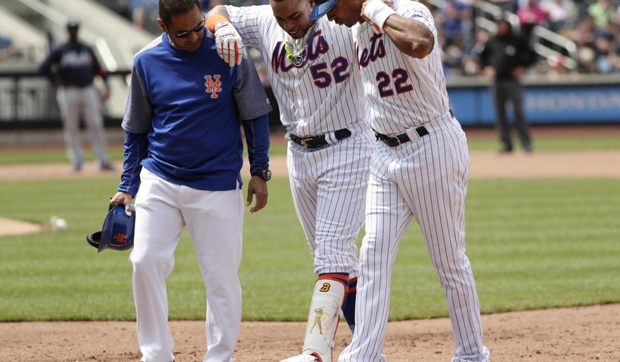 New York Mets' Yoenis Cespedes (52) is helped off the field by first base coach Tom Goodwin (22) and a trainer during the fourth inning of a baseball game against the Atlanta Braves, Thursday, April 27, 2017, in New York. (AP Photo/Frank Franklin II)