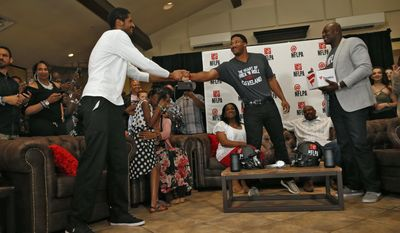 Texas A&M's Myles Garrett, center, is congratulated by his brother and former NBA player Sean Williams, left, and Bruce Smith, right, after Garrett was chosen with the No. 1 pick in the NFL football draft by the Cleveland Browns, at Terre Verde Golf Course in Arlington, Texas, Thursday, April 27, 2017. (Nathan Hunsinger/The Dallas Morning News via AP)