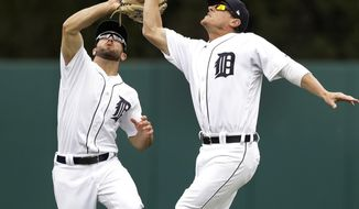 Detroit Tigers center fielder Tyler Collins, left, and right fielder Jim Adduci chase a ball hit by Seattle Mariners designated hitter Nelson Cruz during the sixth inning of a baseball game, Thursday, April 27,2017, in Detroit. (AP Photo/Carlos Osorio)