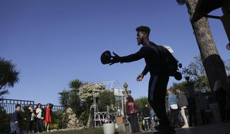 Michigan's Nick Eubanks throws a football with a young Italian boy after a day at Ninfe Beach on Lake Albano, about 16 miles southeast of Rome, Tuesday, April 25, 2017. Michigan's NCAA college football team arrived in Rome last weekend and kicked off the unique trip by meeting with refugees before going to the Vatican for a Papal address before practicing a few times. (Romain Blanquart/Detroit Free Press via AP)