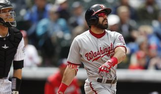 Washington Nationals' Adam Eaton watches his solo home run in front of Colorado Rockies catcher Dustin Garneau during the fifth inning of a baseball game Thursday, April 27, 2017, in Denver. Washington won 16-5. (AP Photo/David Zalubowski)