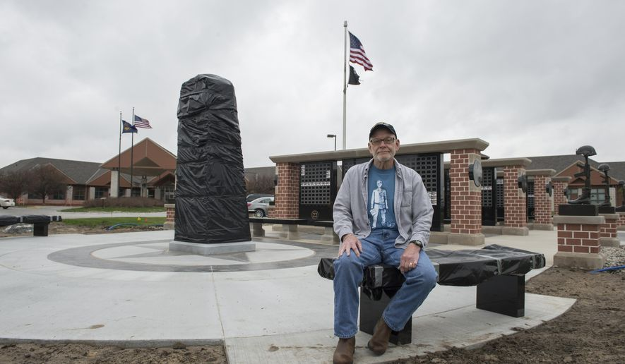 In an April 17, 2017 photo, Bruce Bounds poses for a photo with a Vietnam memorial statue that will be unveiled at the Norfolk Veterans Home. The idea behind the memorial and its design came from Bounds, who served as a U.S. Navy corpsman in Vietnam.  (Jake Wragge/The Norfolk Daily News via AP)