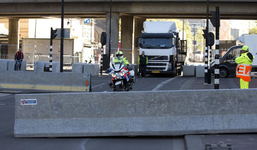 A police motorcycle passes road blocks preventing cars and trucks from accessing the route Dutch King Willem-Alexander will use as he attends Kingsday celebrations in Tilburg, south central Netherlands, Thursday, April 27, 2017. (AP Photo/Peter Dejong)