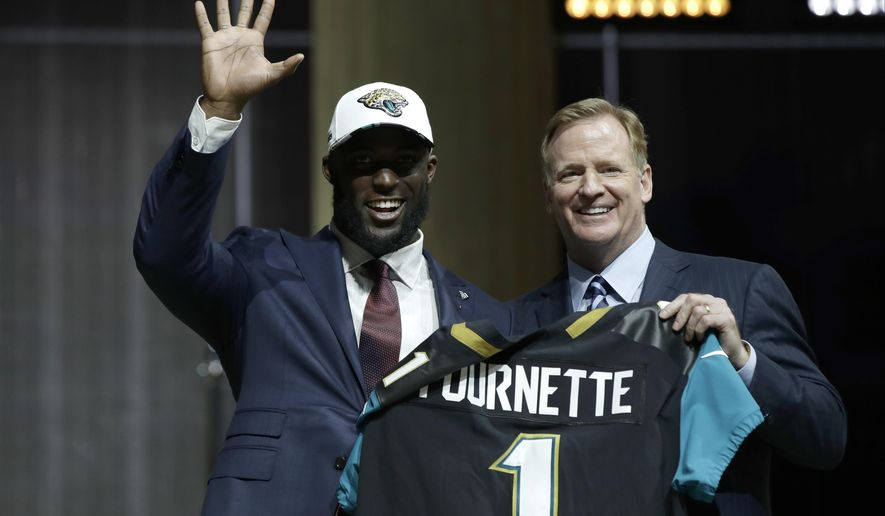 LSU's Leonard Fournette, left, waves as he poses with NFL commissioner Roger Goodell after being selected by the Jacksonville Jaguars during the first round of the 2017 NFL football draft, Thursday, April 27, 2017, in Philadelphia. (AP Photo/Matt Rourke)