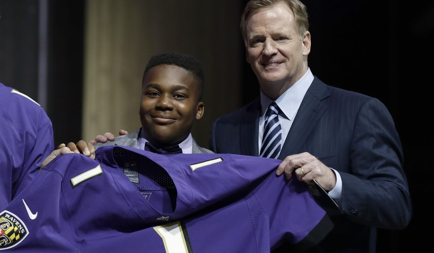 T.J. Owuanibe, 14, left, poses with NFL commissioner Roger Goodell after announcing the Baltimore Ravens' selection during the first round of the 2017 NFL football draft, Thursday, April 27, 2017, in Philadelphia. (AP Photo/Matt Rourke)