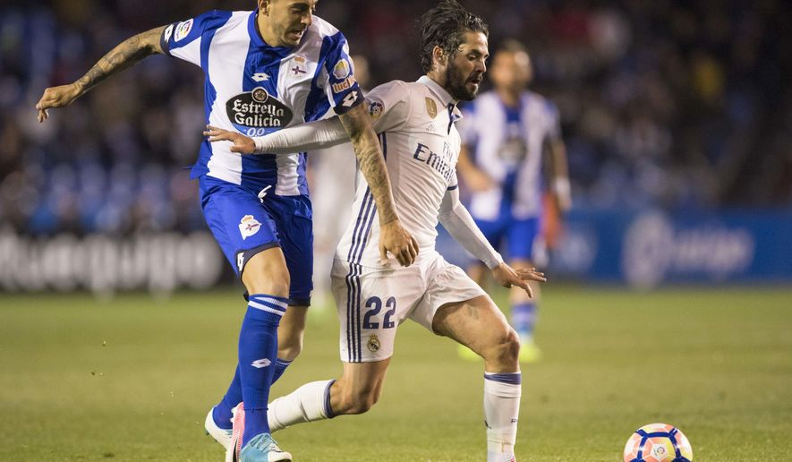 Deportivo's Joselu challenges with Real Madrid's Isco, right, during a Spanish La Liga soccer match between Deportivo La Coruna and Real Madrid at the Riazor stadium in A Coruna, Spain, Wednesday April 26, 2017. (AP Photo/Lalo R. Villar)