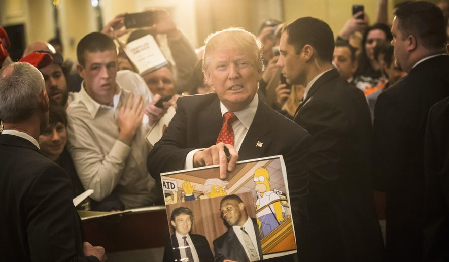 """In this Jan. 29, 2016, file photo, Republican presidential candidate Donald Trump holds depictions of himself on, """"The Simpsons"""" and a photo with boxer Mike Tyson, given to him by an attendee during a campaign stop at the Radisson Hotel in Nashua, N.H. """"The Simpsons"""" released a short online clip on April 26, 2017, mocking President Donald Trump ahead of his 100th day in office. (AP Photo/John Minchillo, File)"""