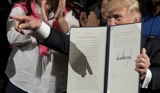 """President Donald Trump holds up an Executive Order on """"Improving Accountability and Whistleblower Protection"""" after signing it at the Department of Veterans Affairs, Thursday, April 27, 2017, in Washington. (AP Photo/Andrew Harnik)"""