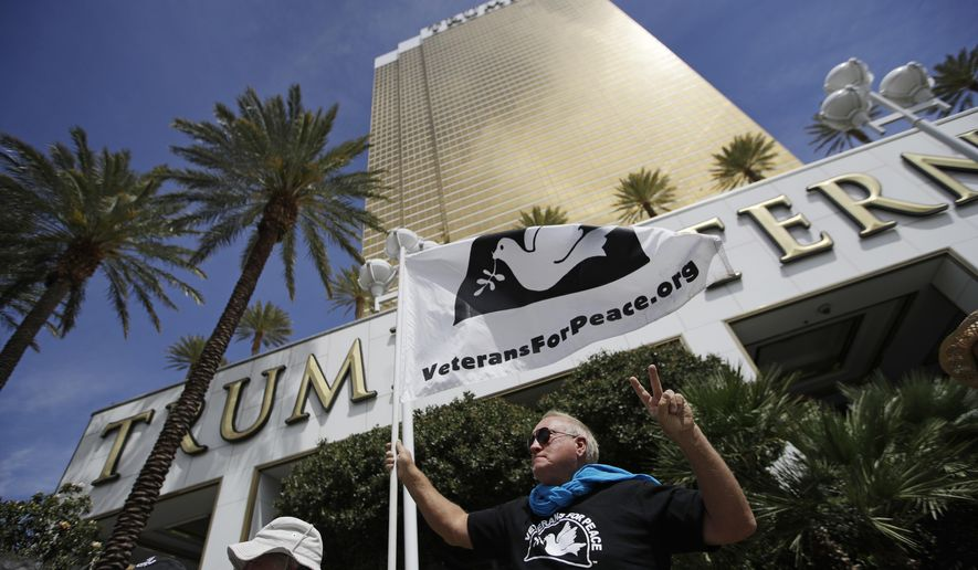 Chris Knudson holds up a flag during a protest against drone warfare outside of the Trump International hotel Thursday, April 27, 2017, in Las Vegas. The protest was held a day after a man was accused of trying to set fire to the property. The incidents are just the latest targeting the president's gold glass tower just off the Las Vegas Strip. (AP Photo/John Locher)