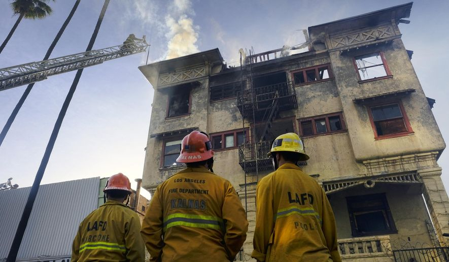 Los Angeles fire department firefighters look on as the last embers of a fire are doused at an apartment building in Los Angeles on Thursday, April 27, 2017. The fire raged through two vacant apartment buildings and forced evacuation of a convalescent hospital west of downtown. The fire roared through a two-story apartment building and an old four-story apartment building for nearly 90 minutes before firefighters knocked down the flames. (AP Photo/Richard Vogel)
