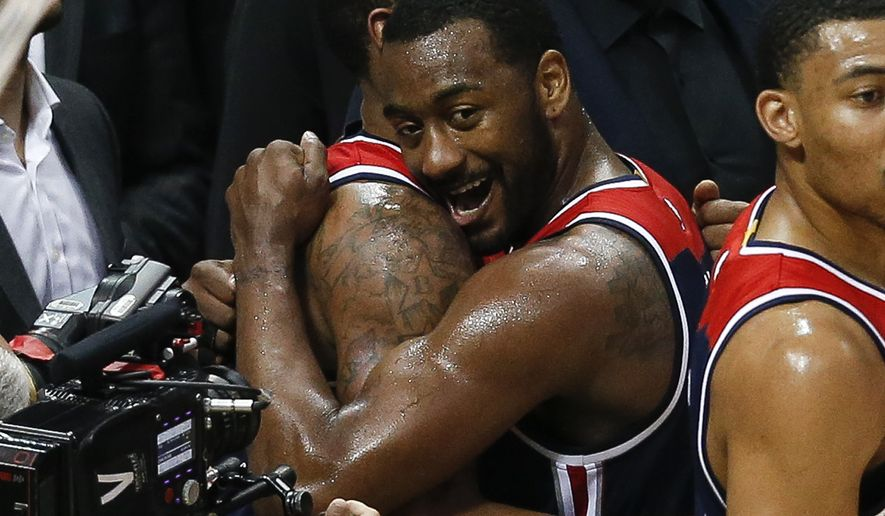 Washington Wizards guard John Wall, right, hugs teammate Bradley Beal in the closing moments of Game 6 of a first-round NBA playoff basketball series against the Atlanta Hawks, Friday, April 28, 2017, in Atlanta. (AP Photo/John Bazemore)
