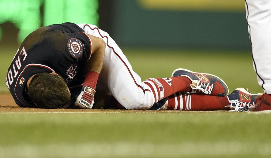Washington Nationals' Adam Eaton (2) lies on the field after he was injured on a play at first base during the ninth inning of a baseball game against the New York Mets, Friday, April 28, 2017, in Washington. (AP Photo/Nick Wass)