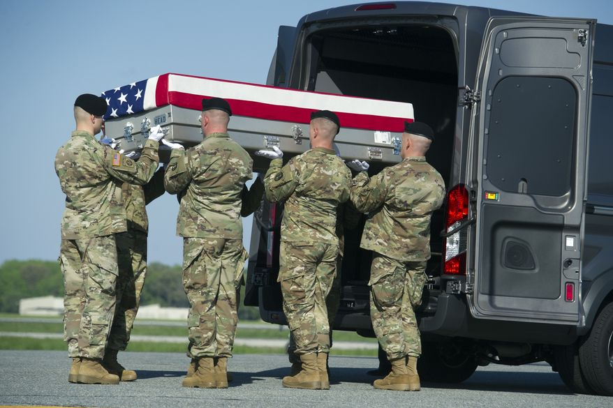 An Army carry team places a transfer case containing the remains of Army Sgt. Cameron Thomas, 23, of Kettering, Ohio, into the transfer vehicle, Friday, April 28, 2017, at Dover Air Force Base, Del. Thomas and Sgt. Joshua P. Rodgers, 22, of Bloomington, Ill, killed during a raid on an Islamic State compound in eastern Afghanistan, may have died as a result of friendly fire during the opening minutes of the fierce, three-hour firefight, the Pentagon said Friday. (AP Photo/Cliff Owen)