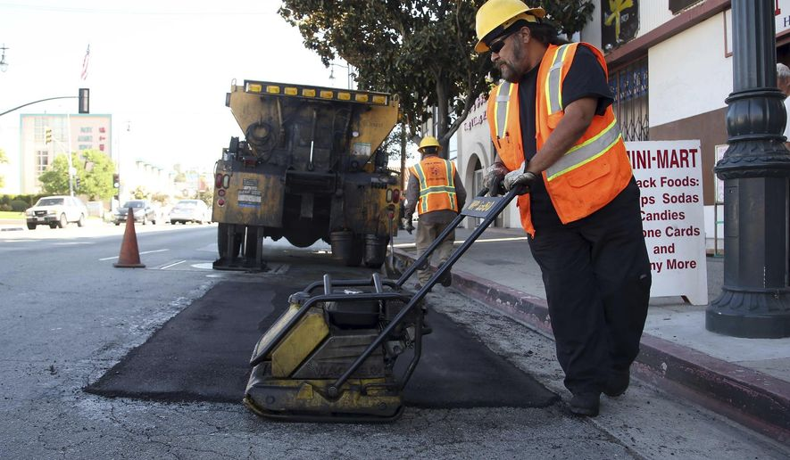 ADDS LOCAL PROJECTS COULD START SOONER - FILE - In this Sept. 11, 2014 file photo, city worker Ralph Mendoza repairs a street in downtown Los Angeles. California drivers will see their gas prices rise in November 2017 and will pay more to register their vehicles come January. The California Transportation Commission prioritize projects for the funding and the first construction work will likely begin in the summer of 2018, said Mark Dinger, a spokesman for Caltrans. However, local projects could get off the ground sooner, said Randy Breault, a public works director in Brisbane who serves on the board of directors for the California League of Cities. (AP Photo/Nick Ut, File)