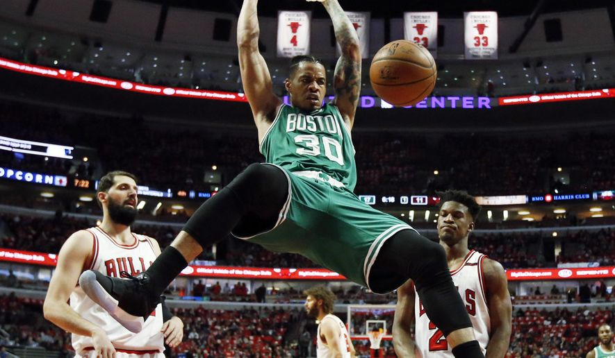 Boston Celtics' Gerald Green (30) dunks as Chicago Bulls' Nikola Mirotic, left, and Jimmy Butller react during the first half in Game 6 of an NBA basketball first-round playoff series, Friday, April. 28, 2017, in Chicago. (AP Photo/Nam Y. Huh)