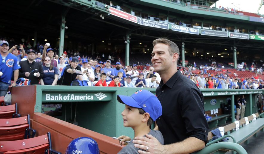 Theo Epstein, president of baseball operations for the Chicago Cubs, poses with a young fan prior to a baseball game between the Boston Red Sox and the Cubs at Fenway Park, Friday, April 28, 2017, in Boston. Epstein is a former general manager for the Red Sox. (AP Photo/Elise Amendola)