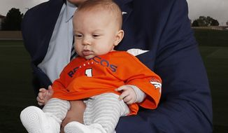 Denver Broncos first-round selection in the NFL draft offensive tackle Garett Bolles poses with his 4-month-old son, Kingston, at the team's headquarters Friday, April 28, 2017, in Englewood, Colo. (AP Photo/David Zalubowski)