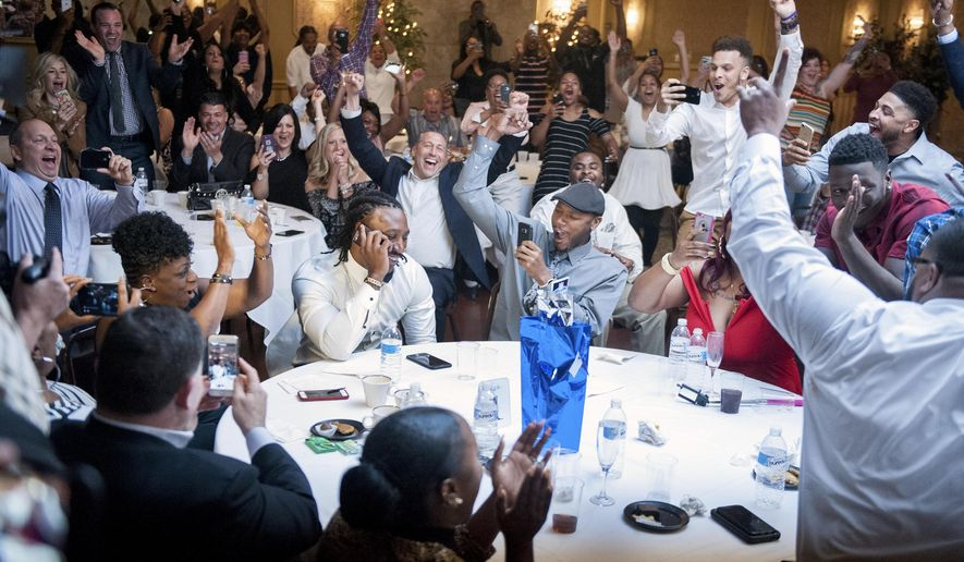 The room erupts around Malik Hooker, center left, still on the phone with the Indianapolis Colts, as it is announced on television that he had been selected by the Colts with the 15th pick in the first round of the NFL football draft, Thursday, April 27, 2017 in New Castle, Pa. (Haley Nelson/Pittsburgh Post-Gazette via AP)