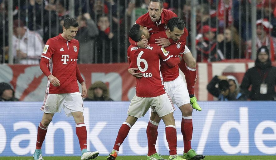 Bayern's Mats Hummels, right, celebrates with team mates Franck Ribery, top, and Thiago after scoring his side's second goal during the German Soccer Cup semifinal match between FC Bayern Munich and Borussia Dortmund at the Allianz Arena stadium in Munich, Germany, Wednesday, April 26, 2017. (AP Photo/Matthias Schrader)