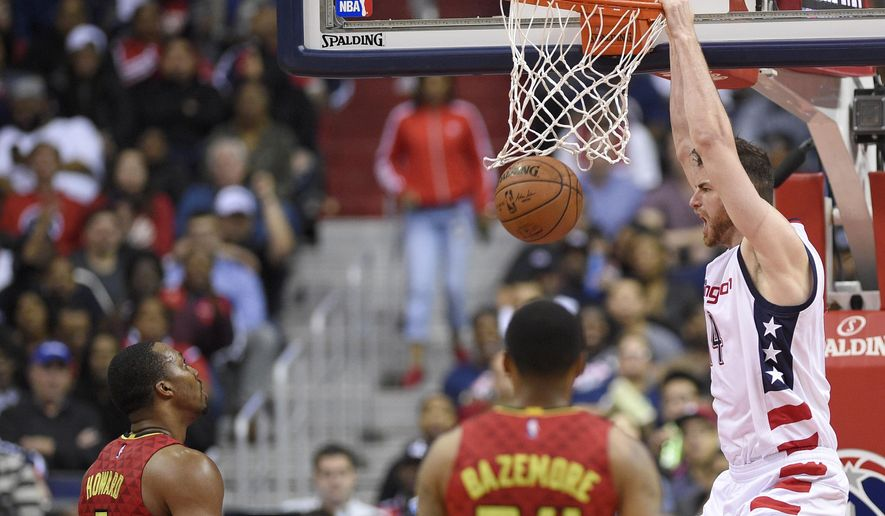 Washington Wizards forward Jason Smith (14) dunks against Atlanta Hawks center Dwight Howard (8) and forward Kent Bazemore (24) during the second half in Game 5 of a first-round NBA basketball playoff series, Wednesday, April 26, 2017, in Washington. The Wizards won 103-99. (AP Photo/Nick Wass)
