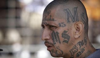 FILE - In this March 26, 2012 file photo a gang member of MS-13 attends mass at a prison in Ciudad Barrios, El Salvador. MS-13, or the Mara Salvatrucha, is believed by federal prosecutors to have thousands of members across the U.S., primarily immigrants from Central America. It has a stronghold in Los Angeles, where it emerged in the 1980s as a neighborhood street gang. (AP Photo/Luis Romero, File)
