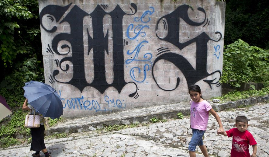 In this Aug. 21, 2014, file photo, a family walks by a wall covered by a symbol from the Mara Salvatrucha, of MS-13 gang in Ilopango, El Salvador. In communities across El Salvador, the Mara Salvatrucha and their arch-rivals, the 18th Street Gang, are de facto rulers. (AP Photo/Esteban Felix, File)