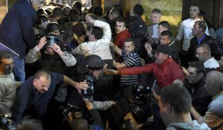 Protestors clash with police to enter into the parliament building in Skopje, Macedonia, Thursday, April 27, 2017. Chaos swept into Macedonia's parliament Thursday as demonstrators stormed the building and attacked lawmakers to protest the election of a new speaker despite a months-old deadlock in efforts to form a new government. (AP Photo/Dragan Perkovski)