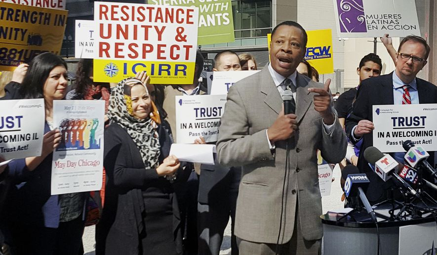 In this April 24, 2017 photo, Pastor Don Taylor, of a suburban Chicago organizing group, speaks to immigrant rights advocates in downtown Chicago. The advocates plan to march in a May 1 rally in Chicago. (AP Photo by Sophia Tareen)
