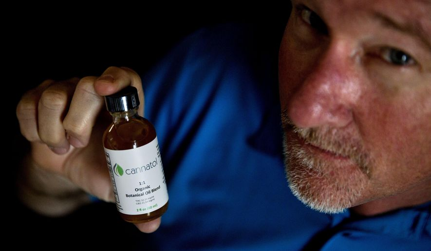 In this Monday, April 17, 2017 photo, Georgia State Rep. Allen Peake, R - Macon, displays a bottle of cannabis oil in his office in Macon, Ga. Peake is at the center of a semi-legal statewide medical cannabis distribution network. Though he successfully championed the creation and expansion of the medical marijuana program in Georgia, there is still no legal way for patients to obtain the low-THC cannabis oil. So Peake is taking matters into his own hands. (AP Photo/David Goldman)