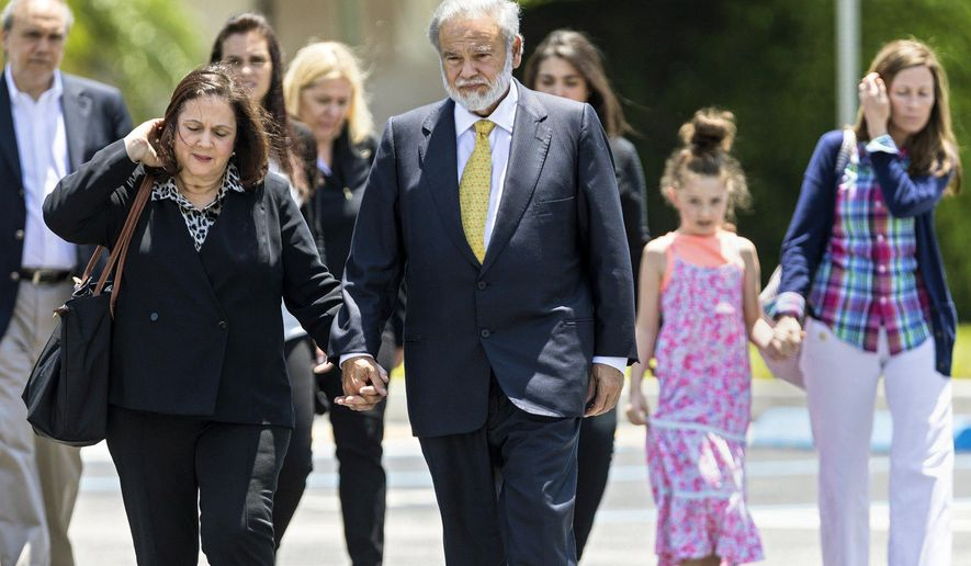 Dr. Salomon Melgen holds hands with his wife, Flor, as he leaves the federal courthouse with family and friends after arriving for a jury question Friday, April 28, 2017. Melgen, a prominent Florida eye doctor accused of political corruption was convicted of Medicare fraud Friday, increasing the odds that federal prosecutors could pressure him to testify against New Jersey Democratic Sen. Bob Menendez. (Lannis Waters /Palm Beach Post via AP)