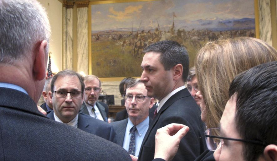 Montana House Speaker Austin Knudsen stands in the center of   legislators after the House voted down an infrastructure package for the fifth time on Friday, April 28, 2017, in Helena, Mont. The Montana Legislature plans to adjourn later Friday, with or without the $80 million infrastructure bill that has become the most contentious issue of the legislative session. (AP Photo/Matt Volz)