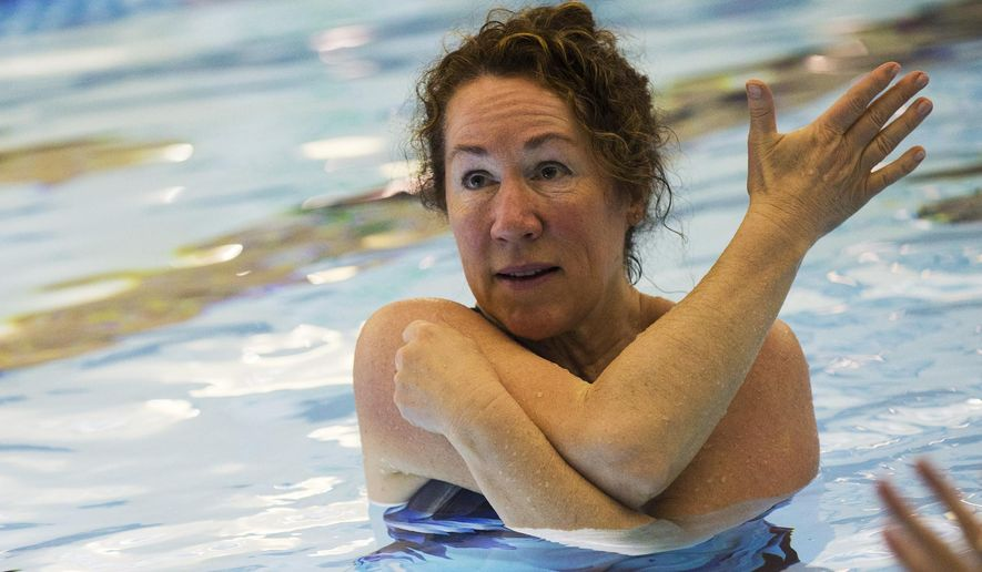 ADVANCE FOR RELEASE SATURDAY, APRIL 29, 2017, AT 12:01 A.M. MDT - In this April 19, 2017, photo, Sara Andre stretches her arm during a multiple sclerosis water class at the Kroc Center in Coeur d'Alene, Idaho. (Loren Benoit/Coeur D'Alene Press via AP)