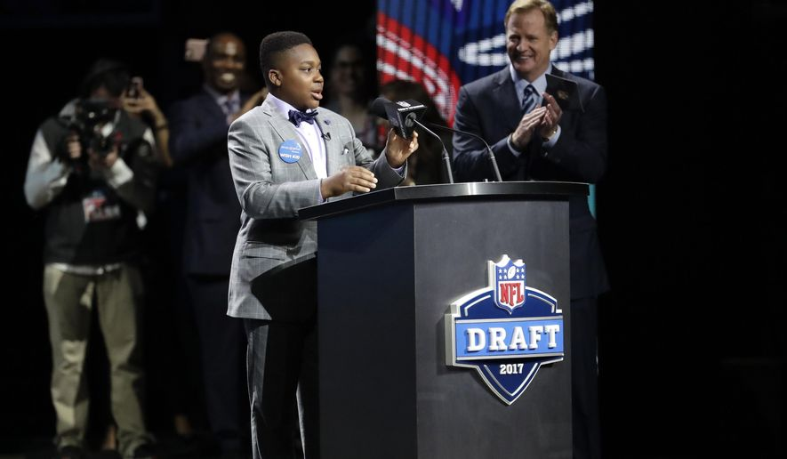 T.J. Owuanibe, 14, announces the Baltimore Ravens' selection during the first round of the 2017 NFL football draft, Thursday, April 27, 2017, in Philadelphia. (AP Photo/Julio Cortez)