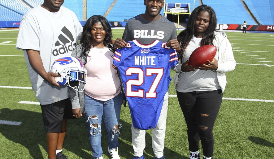 Buffalo Bills; first-round NFL football draft pick Tre'Davious White, second from right, poses with, from left to right, his father, David White, mother, LaShawnita Ruffins, and sister, La'Daijah White, following a media conference at New Era Field in Orchard Park, N.Y., Friday, April 28, 2017. (AP Photo/Bill Wippert)