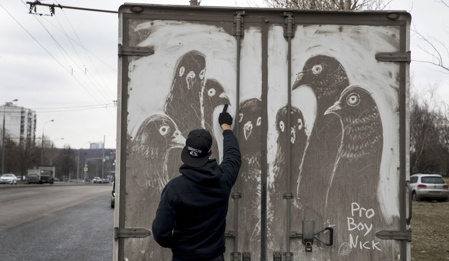 In this photo taken on Saturday, April 22, 2017, artist Nikita Golubev draws pigeons on the back of a dirty delivery truck, in Moscow, Russia. The grimy trucks traversing the polluted and dusty streets of Moscow have inspired Golubev to use white vans and trucks as his canvas to create this ephemeral street art and signs his drawings Pro Boy Nick. (AP Photo/Pavel Golovkin)