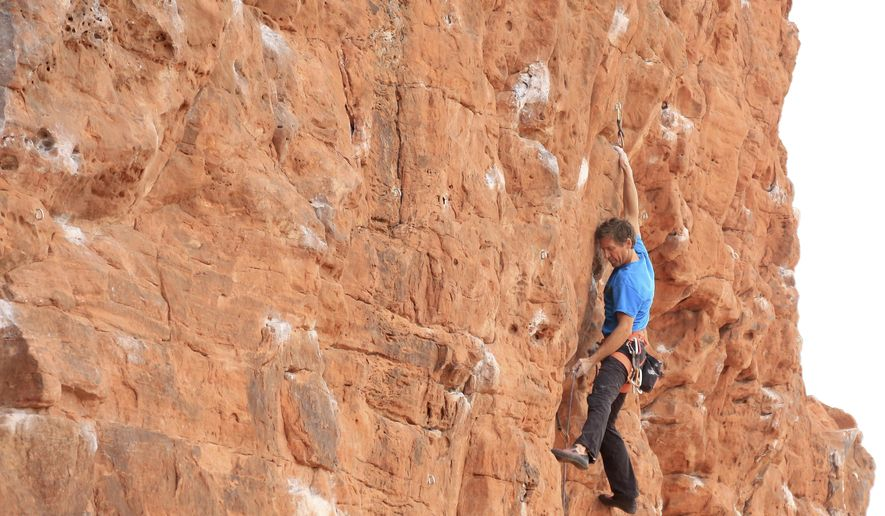 In this April 6, 2017 photo, Todd Perkins climbs along the Chuckwalla Wall in St. George, Utah.  More than 30 routes have been established at this popular climbing spot. (Brian Passey /The Spectrum via AP)