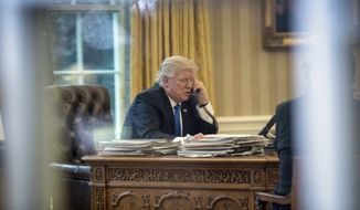 In this Jan. 28, 2017, file photo, President Donald Trump speaks on the phone with German Chancellor Angela Merkel in the Oval Office at the White House in Washington. (AP Photo/Andrew Harnik, File)