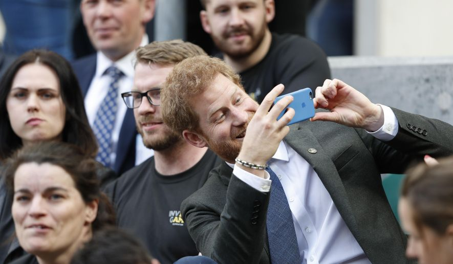Britain's Prince Harry, right, uses a smartphone to take a photograph as he sits with competitors from the 2014 and 2016 Invictus Games in the crowd watching the annual Army Navy armed forces rugby match at Twickenham, west London, on Saturday, April 29, 2017. Prince Harry attended the Army Navy match at Twickenham as Patron of the Invictus Games Foundation, which is the Official Charity of the day for this year's match. The Army Navy Match is the annual rugby union match between the senior XV teams of the Royal Navy and British Army. This year sees the 100th fixture. (Adrian Dennis/ Pool via AP)